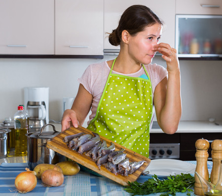 the stinking: woman with foul fish that stinks in domestic interior