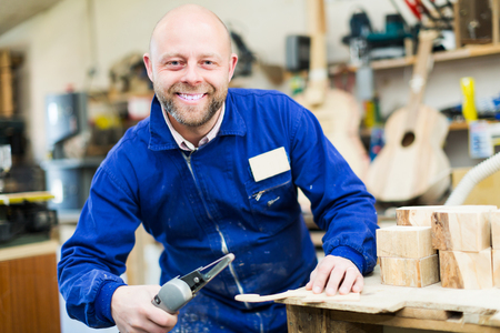 40 45: Portrait of smiling professional woodworker on lathe at musical instrument workroom Stock Photo