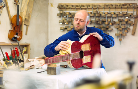 manufactory: Professional worker at guitar manufactory is preparing a guitar for varnishing Stock Photo