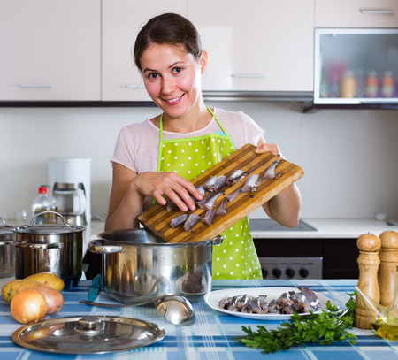25 35: Happy russian housewife trying new recipe of sprattus in kitchen