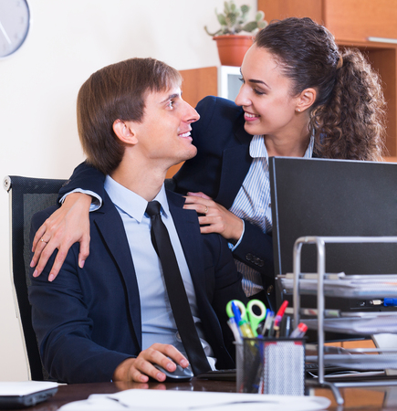 Sexual harassment in office: young female manager flirting with employee at workplace