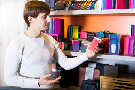 selecting: Adult man selecting new wallet in haberdashery shop Stock Photo