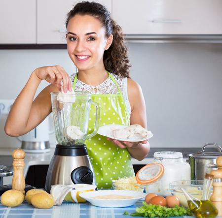 25s: Cheerful girl grinding pate ingredients in blender indoors
