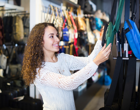 haberdashery: Smiling young brunette choosing new bag in haberdashery shop Stock Photo