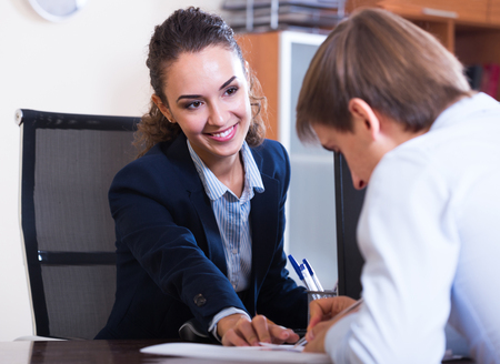 professional practice: portrait of young professional teaching new employee in practice at company