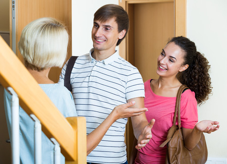 daughter in law: Happy mature mother meets son with his wife at doorway Stock Photo