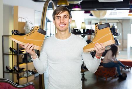 comprando zapatos: Hombre joven sonriente que comprar nuevos zapatos de invierno en una tienda de zapatos Foto de archivo