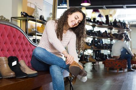 comprando zapatos: sonriendo ruso zapatos de invierno mujer femenina de compra en la tienda de zapatos Foto de archivo
