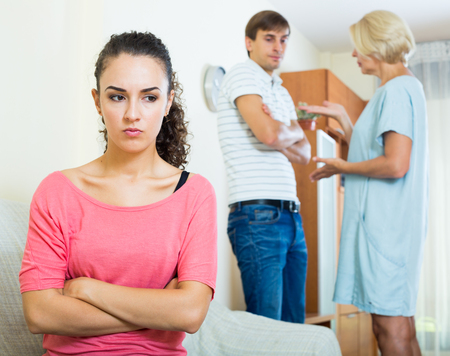 daughter in law: Frustrated young woman taking hard argue between husband and mother