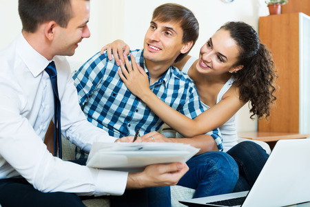 spouses: Happy young spouses and salesman with documents