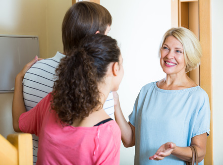 mother in law: Young family couple welcoming senior mother at door and smiling