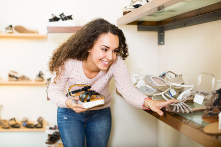 comprando zapatos: Smiling young longhaired brunette buying new summer shoes in a shoe store