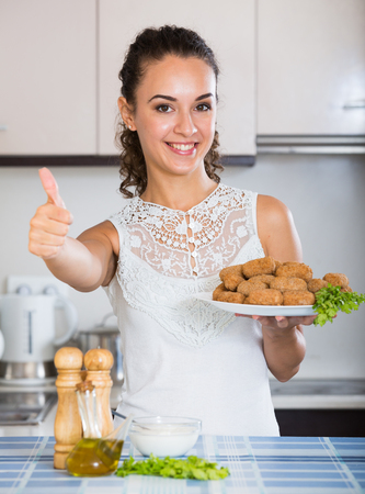 crocchette: Smiling girl with tasty breadcrumbed crocchette in domestic kitchen