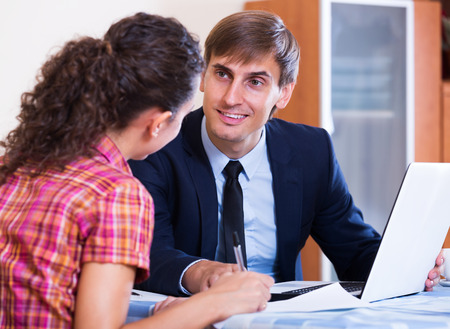 30 35: Positive insurance agent and woman customer discussing agreement terms and smiling indoors
