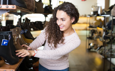 buying shoes: Happy brunette girl buying fashion winter shoes in a shoe store and smiling Foto de archivo
