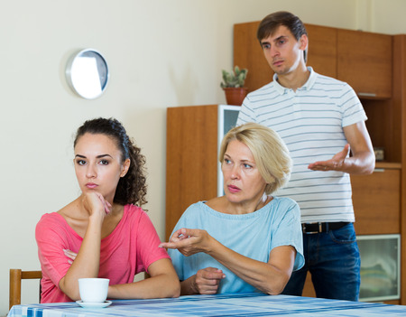 son in law: Offended young woman listening to rebukes from mother and husband