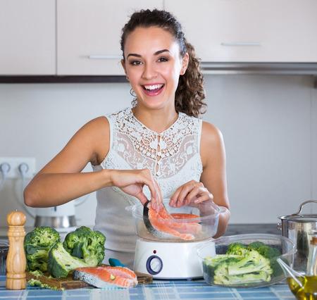 corcovado: Alegre joven Morena vapor salm�n y verduras en la cocina dom�stica