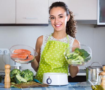 Lächelnde junge Brünette Dämpfen Lachs und Gemüse in Küche
