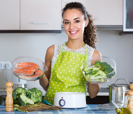 Smiling young brunette steaming salmon and vegetables in domestic kitchen