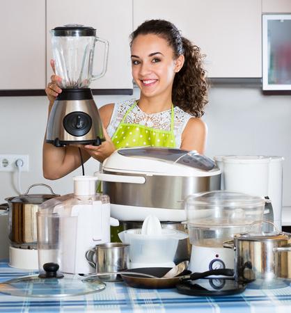 Mujer joven con el procesador de cocina, una olla de cocción lenta y vaporera Foto de archivo