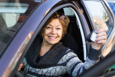 65 70: Portrait of adult american female senior driver smiling in car Stock Photo