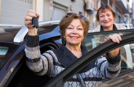 new age: Female driver in golden age standing with new car key outdoor