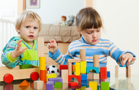 2 3 years: Two siblings together  with blocks in home interior Stock Photo