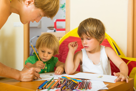 3 4 years: Happy mother and two children sketching on paper in home interior