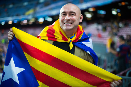 fandom: Smiling male football fan with flag of Catalonia at crowded stadium