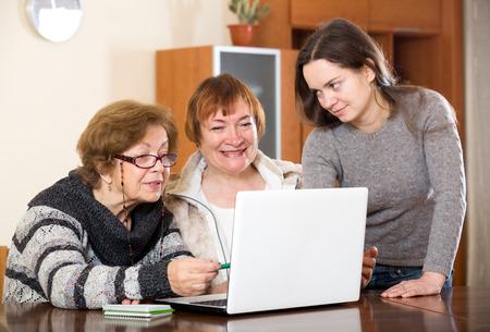 25 35: Attractive girl helping senior women buy something in web Stock Photo
