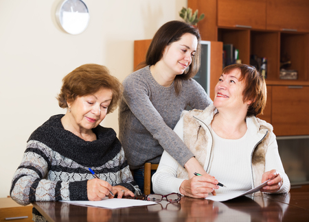 65 70: Portrait of two happy elderly women with papers and agency employee. Focus on girl Stock Photo