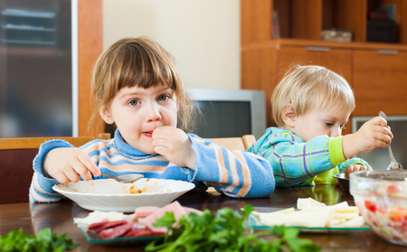 playing with spoon: children eating at wooden table in home interior