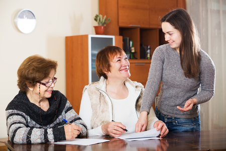 75s: Portrait of positive aged women with papers and agency employee. Focus on standing woman Stock Photo
