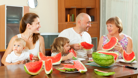 three generations: Smiling three generations family eating watermelon at home interior