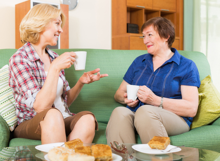 2 50: Two smiling mature female friends drinking tea and gossiping at home