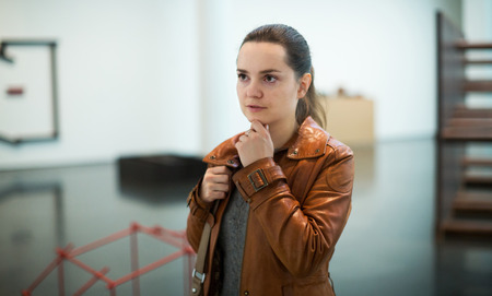 25 35: Portrait of serious young brunette girl in art museum