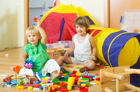 3 4 years: Cheerful little children playing with toys together in home interior Stock Photo
