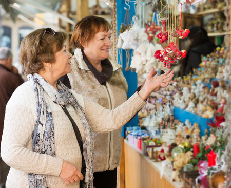 70 75: Cheerful female pensioners buying X-mas decorations at fair. Focus on left person