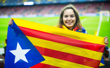 rooting: Excited girl with Catalonia flag rooting for football team