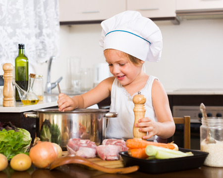3 4 years: Joyful cute little girl cooking with meat and vegetables at home kitchen Stock Photo