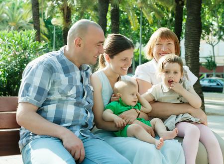 Portrait de trois générations famille heureuse de cinq ans assis au parc