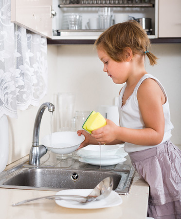 3 4 years: Serious little child washing dishes at domestic kitchen