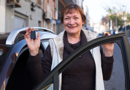 woman in golden age standing with car key outdoor