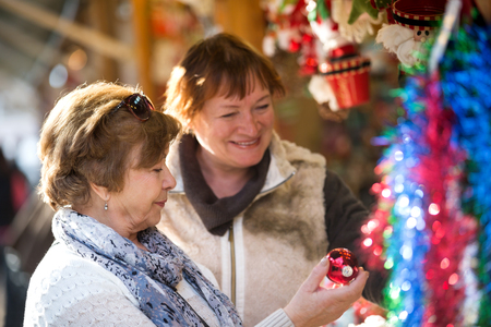 70 75 years: Cheerful senior women walking on the Christmas market and choosing jewelry. Focus on the left woman