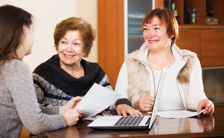 family and friends: Portrait of smiling aged women with papers and agency employee Stock Photo