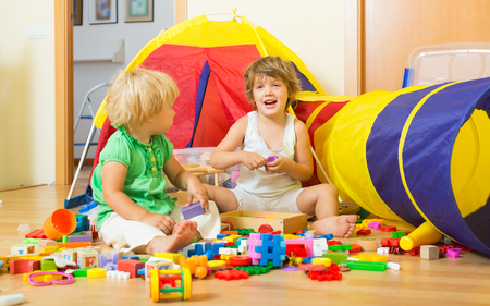 erector: Two happy ?ute little sisters playing with toys together at home Stock Photo
