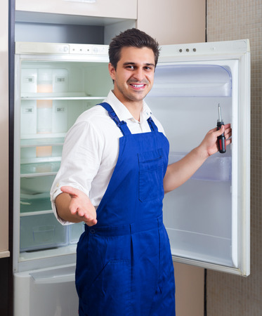 refrigerator kitchen: Happy handyman repairing refrigerator in domestic kitchen