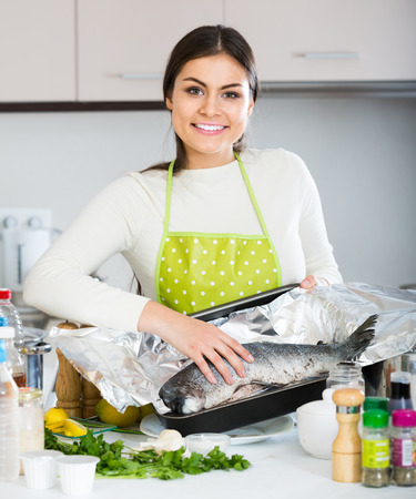 jorobado: Pretty american  girl putting salmon fish in tray for baking