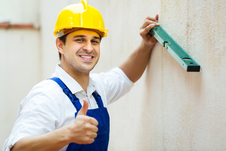 Portrait of happy young specialist making wall plane in new building