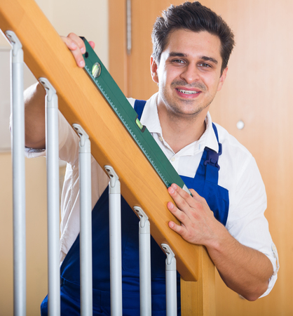constructor: Professional constructor with clinometer near new staircase in apartment